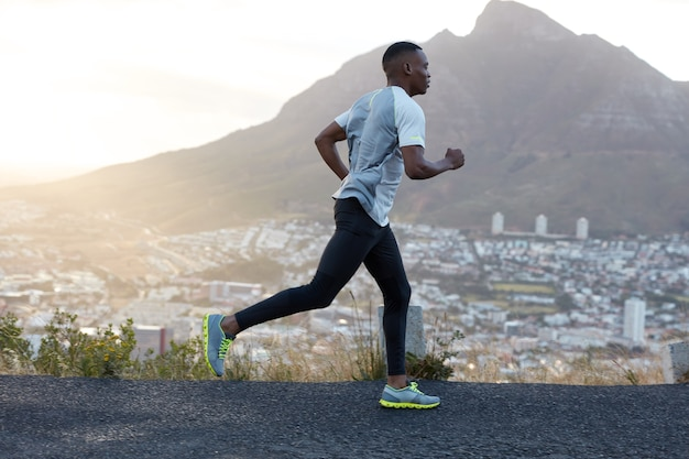 Zelfbepaalde, donkere sportieve mannelijke hardloper draagt sportkleding, loopt lange afstanden over bergwegen, geniet van frisse lucht, voelt zich energiek en gemotiveerd. mensen, levensstijl en sportconcept Gratis Foto