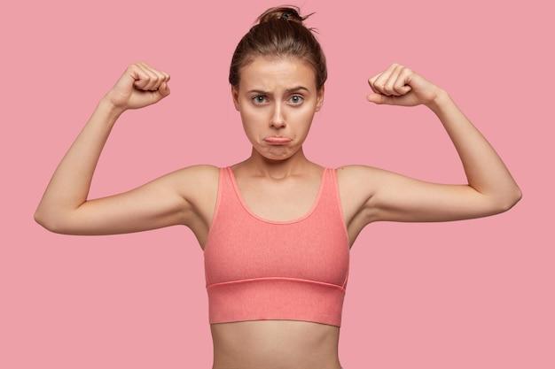 Zelfbepaalde fit vrouw met sportief lichaam, toont spieren, draagt casual top, portemonnees lippen Gratis Foto