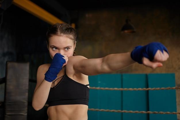 Zelfbepaalde jonge vrouw professionele bokser met sterke gespierde armen en buik dragen zwarte sporttop en blauwe boksbandages mastering ponsen techniek in sportschool Gratis Foto