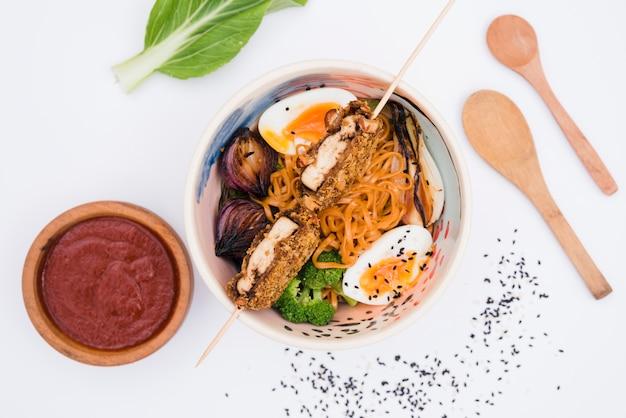 Zelfgemaakt aziatisch japans eten met saus; houten lepel en sesamzaadjes op witte achtergrond Gratis Foto