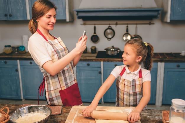 Zelfgemaakt gebak koken. de gelukkige houdende van familie bereidt samen bakkerij voor. moeder en kind dochter meisje zijn koekjes koken en plezier in de keuken. rol het deeg uit. Premium Foto