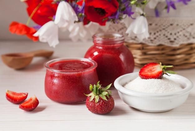 Zelfgemaakte aardbeienjam in de glazen pot en mand met zomerbloemen op de houten tafel Premium Foto