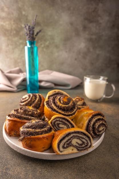 Zelfgemaakte broodjes met maanzaad op een witte plaat kom met lavendel en pet met melk op een donkere achtergrond close-up selectieve aandacht Premium Foto