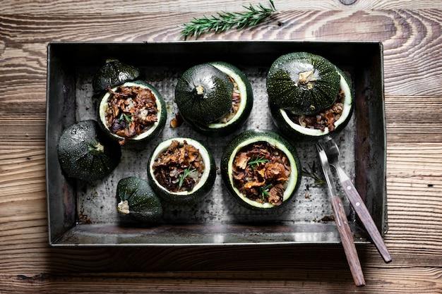 Zelfgemaakte cantharel gevuld ronde courgette op houten tafel Gratis Foto