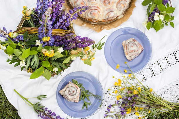 Zelfgemaakte cinnabon-broodjes in romige glazuur tijdens een zomerse picknick Premium Foto