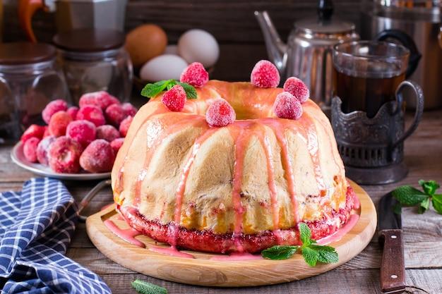 Zelfgemaakte gistcake met aardbeienjam op een oude houten tafel Premium Foto