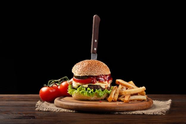 Zelfgemaakte hamburger close-up met rundvlees, tomaat, sla, kaas en frietjes op snijplank. in de burger stak een mes Premium Foto