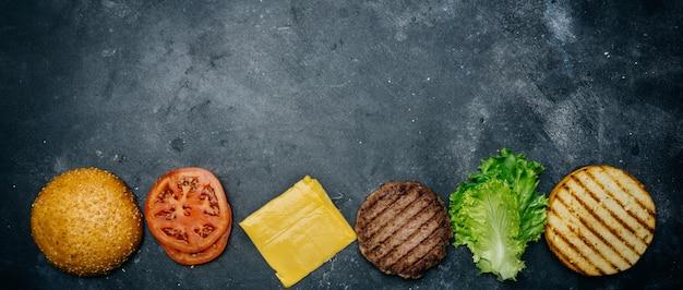 Zelfgemaakte hamburgersamenstelling (recept). producten voor de klassieke burger op een donkere achtergrond. Premium Foto