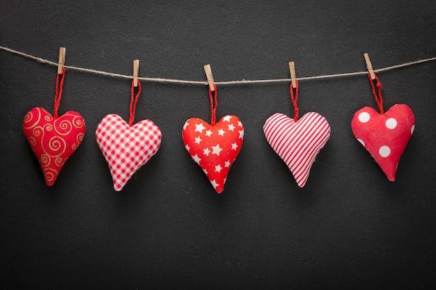 Zelfgemaakte harten aan een touw op een donkere muur. valentines concept Premium Foto
