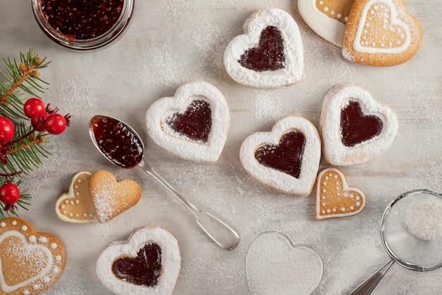 Zelfgemaakte hartvormige koekjes met frambozenjam op witte houten tafel voor kerstmis of valentijnsdag. bovenaanzicht Premium Foto