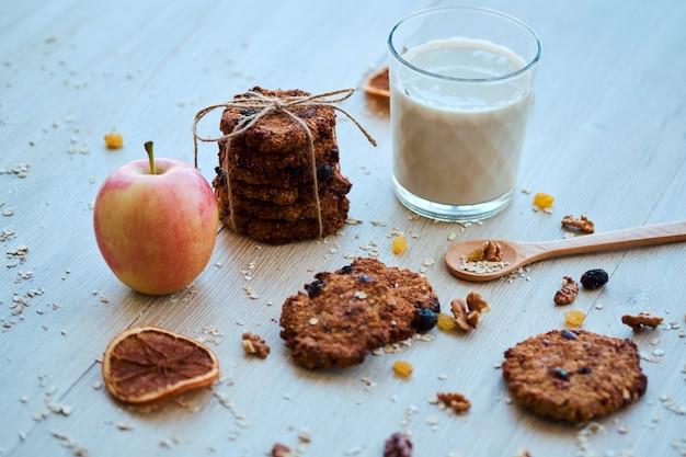 Zelfgemaakte havermoutkoekjes met walnoot, rozijnen en melk op een houten tafel Premium Foto