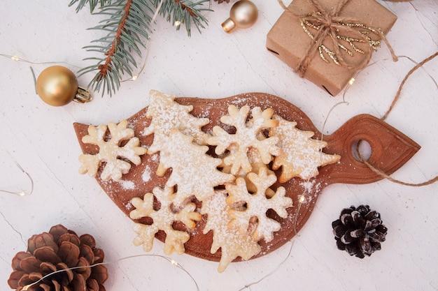 Zelfgemaakte het bakken van kerstmiskoekjes in boom en sneeuwvlokkenvormen Premium Foto