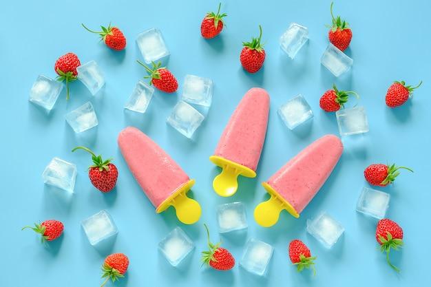 Zelfgemaakte ijslollys. natuurlijk ijs in heldere plastic vormen, aardbeien en ijsblokjes Premium Foto