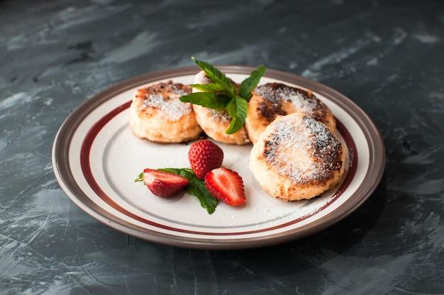 Zelfgemaakte kaas donuts met bessenjam en aardbeien Premium Foto
