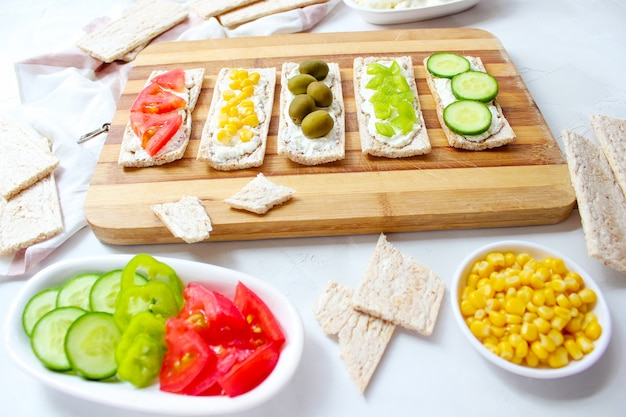Zelfgemaakte knäckebröd toast met kwark en groene olijven, plakjes kool, tomaten, maïs, groene peper op snijplank. gezond voedselconcept, hoogste mening. plat leggen Gratis Foto