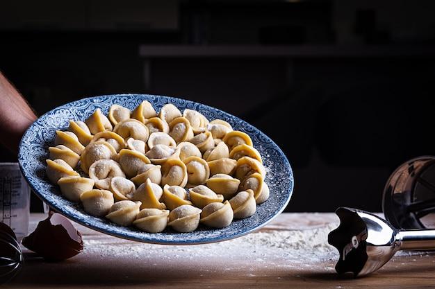 Zelfgemaakte knoedels, pelmeni, ravioli. ruwe russische pelmeni. Premium Foto