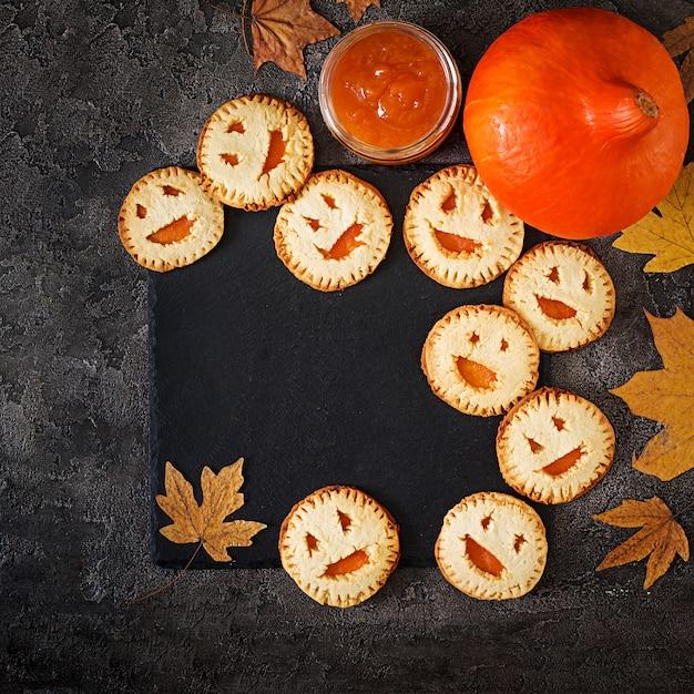 Zelfgemaakte koekjes in de vorm als halloween-hefboom-o-lantaarnpompoenen op de donkere lijst. bovenaanzicht Gratis Foto