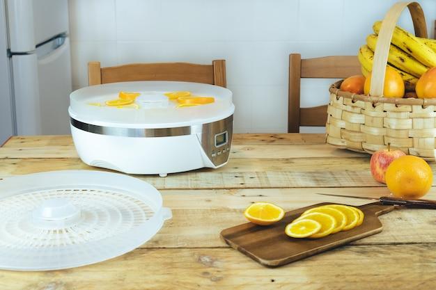 Zelfgemaakte machine om voedsel met stukjes sinaasappel op keukentafel te dehydrateren. Premium Foto
