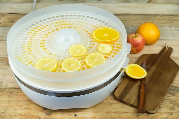 Zelfgemaakte machine om voedsel met stukjes sinaasappel te drogen. Premium Foto