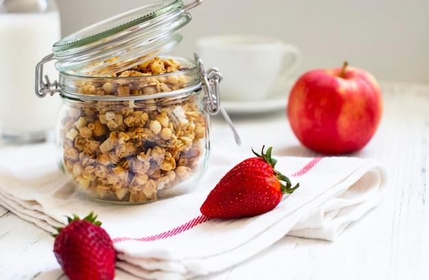 Zelfgemaakte muesli in een glazen pot. ingrediënten voor een gezond ontbijt - muesli, appel, aardbei en melk. detailopname Premium Foto