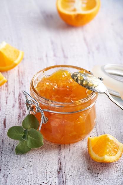 Zelfgemaakte oranje jam in pot op een witte tafel. voedsel achtergrond Premium Foto