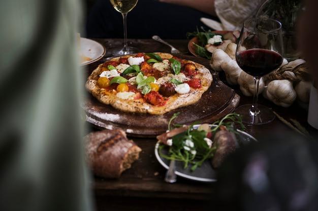 Zelfgemaakte pizza voor het diner met rode wijn Premium Foto