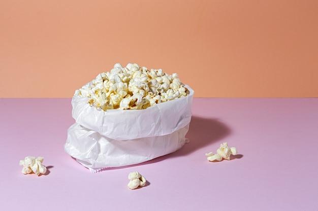 Zelfgemaakte popcorn op gekleurde tafel met hoog contrastlicht. snack concept Premium Foto