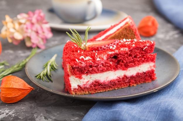 Zelfgemaakte rode fluwelen cake met melkroom en aardbei met kopje koffie Premium Foto