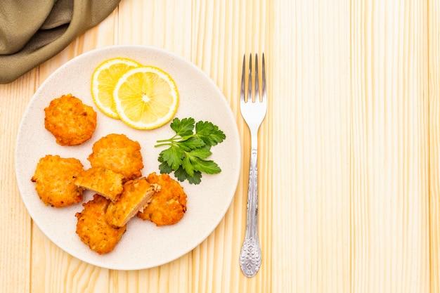 Zelfgemaakte rode viskoekjes met citroen en peterselie in keramische plaat. met stoffen gordijn en vork op houten oppervlak, bovenaanzicht, kopie ruimte. Premium Foto