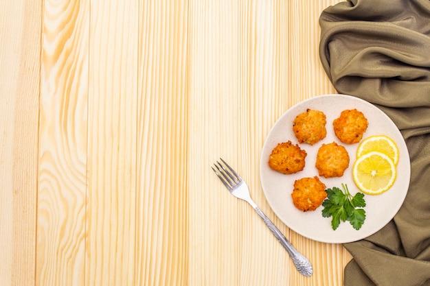 Zelfgemaakte rode viskoekjes met citroen en peterselie in keramische plaat. met stoffen gordijn en vork op houten oppervlak, kopie ruimte, bovenaanzicht. Premium Foto