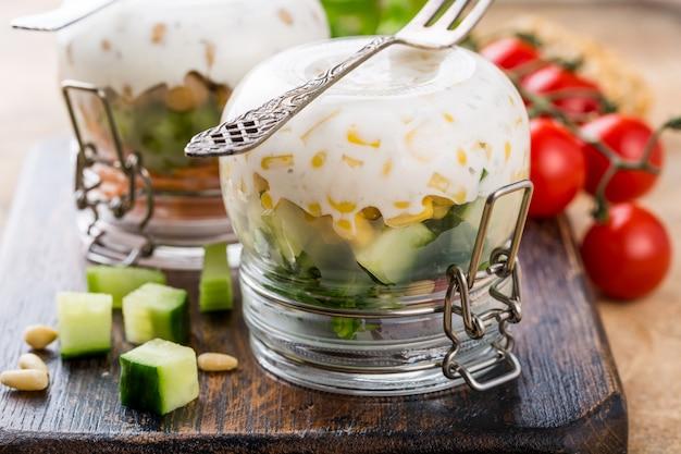 Zelfgemaakte salade in glazen pot ondersteboven op houten snijplank. Premium Foto