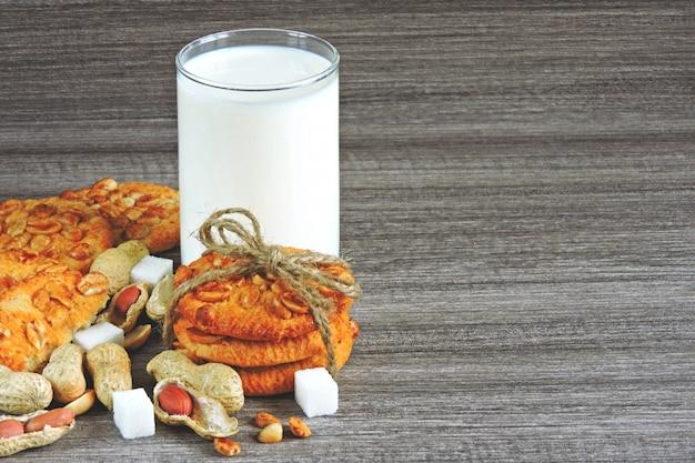 Zelfgemaakte suikerkoekjes met pinda's en een glas verse melk. Premium Foto