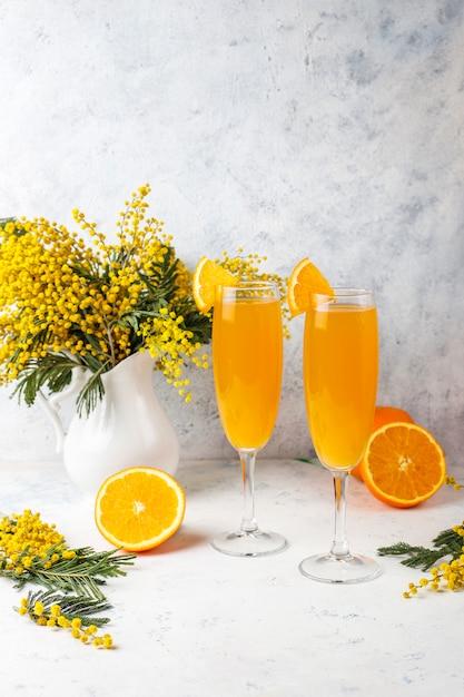Zelfgemaakte verfrissende oranje mimosa-cocktails met champaigne Gratis Foto