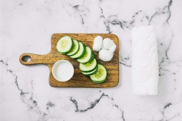 Zelfgemaakte vochtinbrengende crème; plakjes komkommer en katoen op snijplank met handdoek over de marmeren achtergrond Gratis Foto