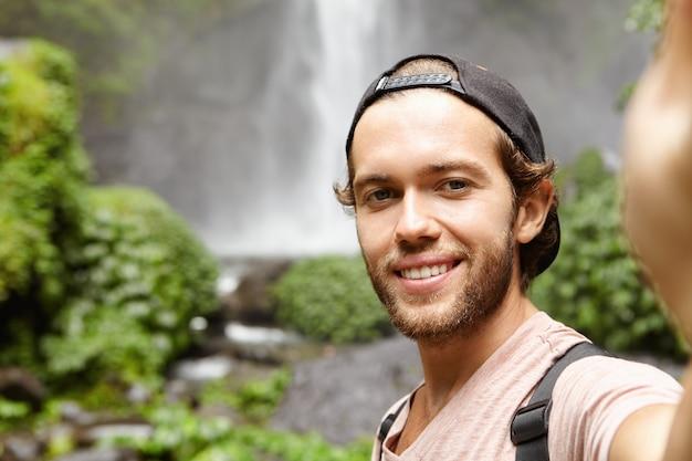 Zelfportret van gelukkige wandelaar in baseball cap selfie te nemen terwijl je tegen waterval in groene exotische bossen. jonge toeristische trekking in het regenwoud tijdens zijn vakantie Gratis Foto