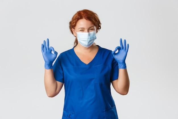 Zelfverzekerd lachende roodharige arts, vrouwelijke verpleegster in medisch masker, handschoenen, oke gebaar tonen, garanderen veilige en kwaliteitscontrole bij kliniek Gratis Foto
