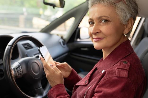 Zelfverzekerd volwassen zakenvrouw in stijlvolle jas chats met haar smartphone in de auto Gratis Foto
