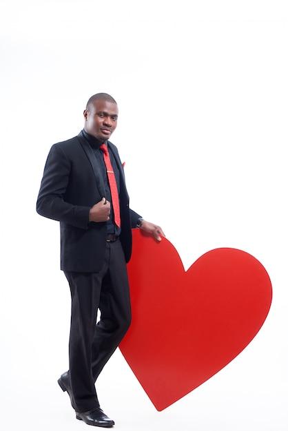 Zelfverzekerde afrikaanse man met elegante suite en rode stropdas leunend met de hand op groot rood hart Gratis Foto