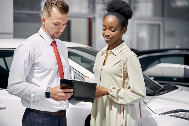Zelfverzekerde blanke man verkoper auto's verkopen bij autodealer Premium Foto