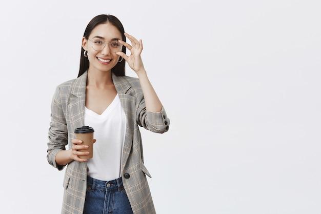 Zelfverzekerde en vrolijke knappe vrouw in glazen en stijlvolle jas, rand aanraken en breed glimlachend terwijl kopje koffie, drank drinken Gratis Foto