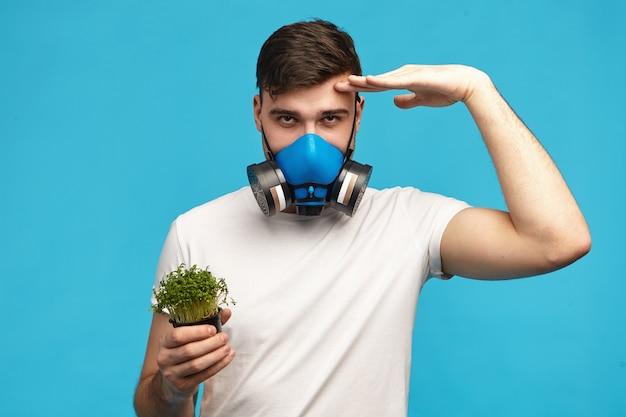 Zelfverzekerde jonge man met gasmasker die hand op zijn voorhoofd houdt als teken dat ze klaar is om je te beschermen tegen pesticiden en genetisch gemodificeerde organismen, met microgreens Gratis Foto
