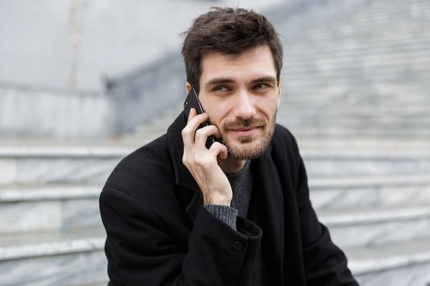 Zelfverzekerde man gekleed in jas zittend aan de straat van de stad, praten over de mobiele telefoon Premium Foto