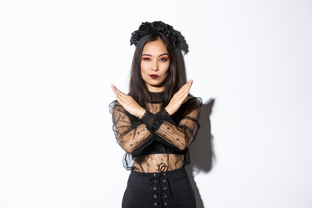 Zelfverzekerde mooie vrouw in zwarte gotische jurk met kruis gebaar, iets slechts afkeuren en stoppen, niet eens met iemand over halloween, staande op witte achtergrond. Gratis Foto
