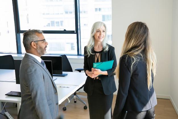 Zelfverzekerde partners bijeen in kantoorruimte, praten en glimlachen. bebaarde baas in brillen project bespreken met mooie zakenvrouwen. bedrijfs-, communicatie- en topmanagementconcept Gratis Foto