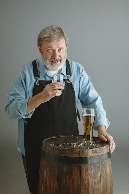 Zelfverzekerde senior man brouwer met zelfgemaakt bier in glas op houten vat op grijze muur Gratis Foto