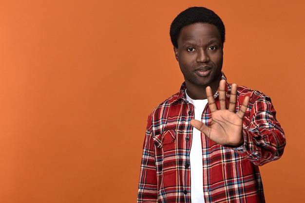 Zelfverzekerde serieuze jonge donkere man met stopbord, geopende handpalm opheffen en nee zeggen stijlvolle afrikaanse man weigert waarschuwingsgebaar met hand voor hem, weigering uitdrukken Gratis Foto