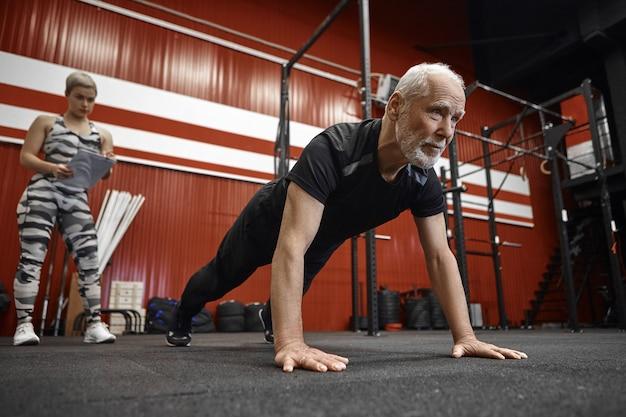 Zelfverzekerde sportieve zestigjarige man met baard doet push-ups in stijlvolle zwarte sportkleding terwijl zijn coach met klembord zijn resultaten opschrijft. leeftijd, pensioen, gezondheid en vitaliteit Gratis Foto