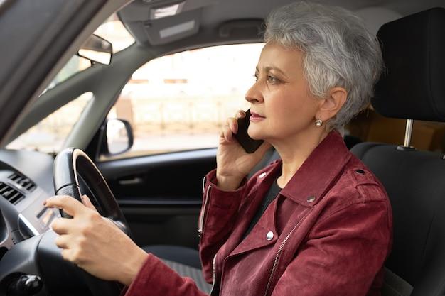 Zelfverzekerde volwassen zakenvrouw in stijlvolle jas auto rijden op straten van de stad en tegelijkertijd spreken op mobiel Gratis Foto