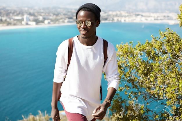 Zelfverzekerde vrolijke jonge zwarte europese mannelijke student met trendy bril en hoed wandelen in de bergen boven de azuurblauwe zee, met de schoonheid van zijn vrienden en bezienswaardigheden van zijn geboortestad aan zee Gratis Foto