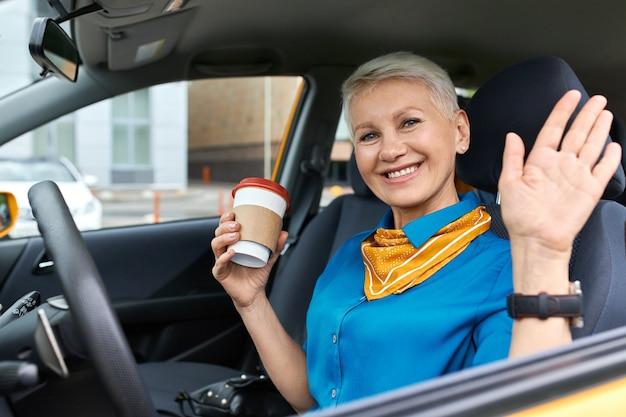 Zelfverzekerde vrolijke rijpe zakenvrouw met kort blond haar, zittend in de schroei van de bestuurder met wegwerp kartonnen beker Gratis Foto